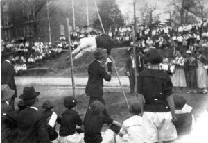 This image is of a High Jump Competition on the Athletic Field in the 1920s. The athletic field was located where the DiGiorgio Center Courtyard is today. The building visible in the background is Peabody Gymnasium which was razed in 2007 and was located where the DiGiorgio Center currently stands.