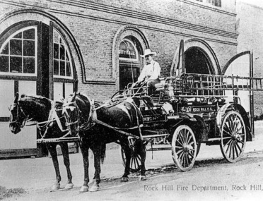 Frank H. Hamilton sitting on Rock Hill's fire wagon in front of Rock Hill's Fire Department at City Hall - nd