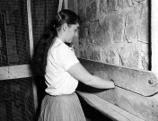 Prison Stocks used for Convicts during Construction of Main Building. Student Nancy Brassington posing with Stocks in 1958.
